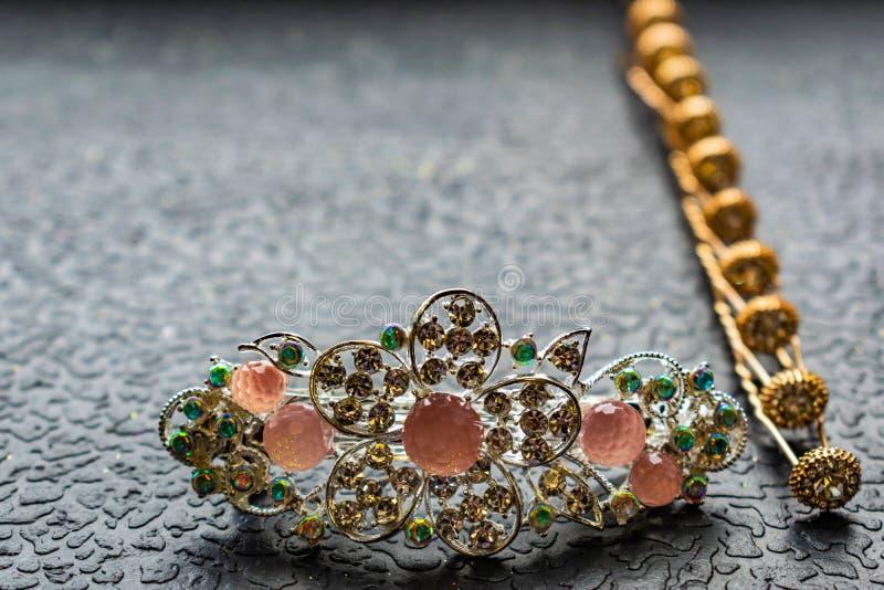 Piękny automatyczny barrette z błyszczącymi kamieniami i różowymi koralikami na zmroku textured tło Złociści hairpins z białymi r obraz stock