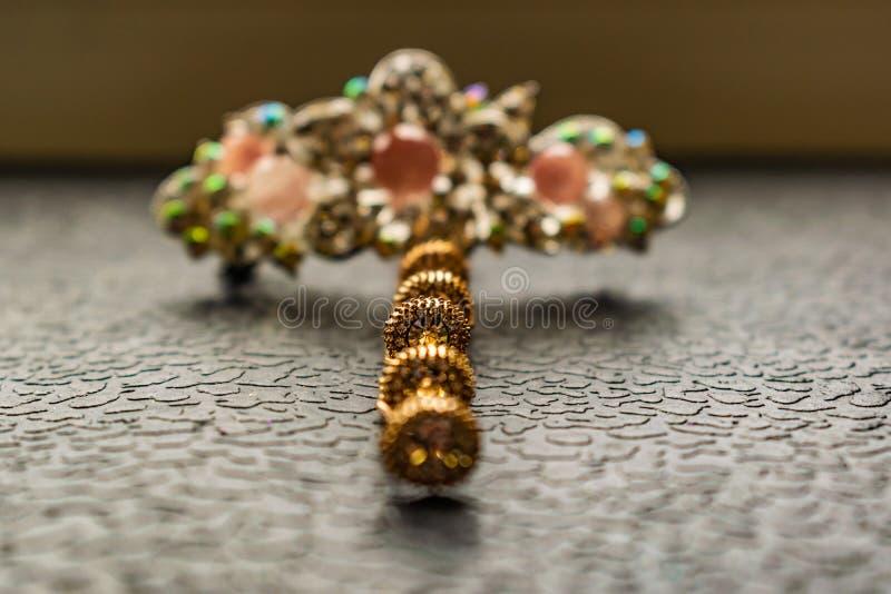 Piękny automatyczny barrette z błyszczącymi kamieniami i różowymi koralikami na zmroku textured tło Złociści hairpins z białymi r obraz royalty free