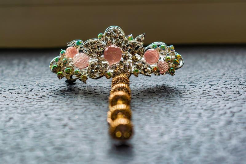 Piękny automatyczny barrette z błyszczącymi kamieniami i różowymi koralikami na zmroku textured tło Złociści hairpins z białymi r fotografia royalty free