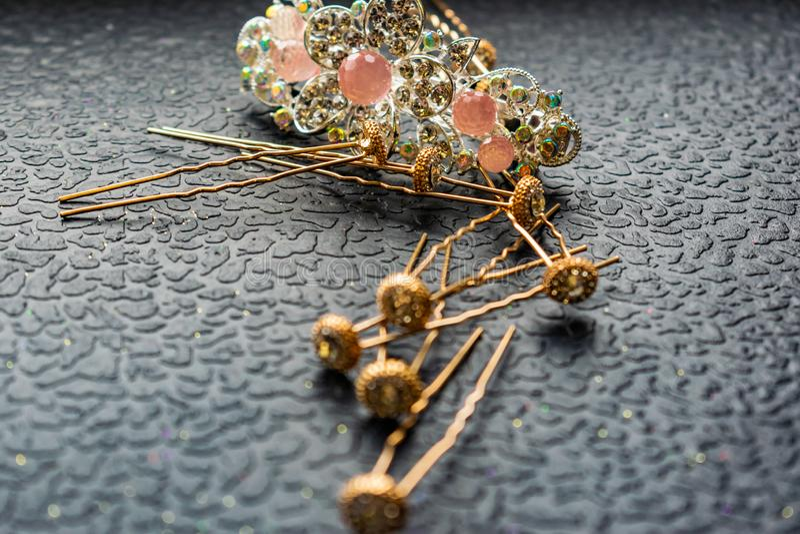 Piękny automatyczny barrette z błyszczącymi kamieniami i różowymi koralikami na zmroku textured tło Złociści hairpins z białymi r zdjęcie royalty free