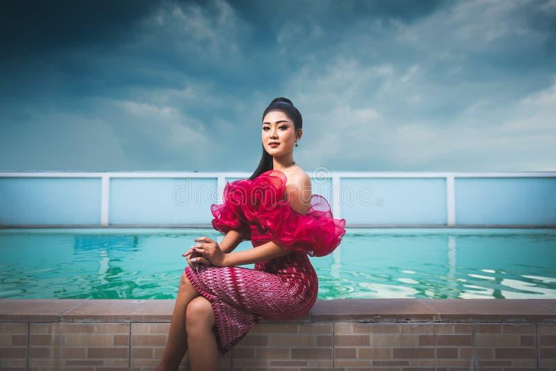 Piękny Azjatycki kobiety obsiadanie obok basenu plenerowego z czerwieni suknią fotografia stock