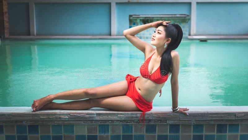 Piękny Azjatycki kobiety obsiadanie obok basenu plenerowego z czerwonym pływackim kostiumem zdjęcia stock