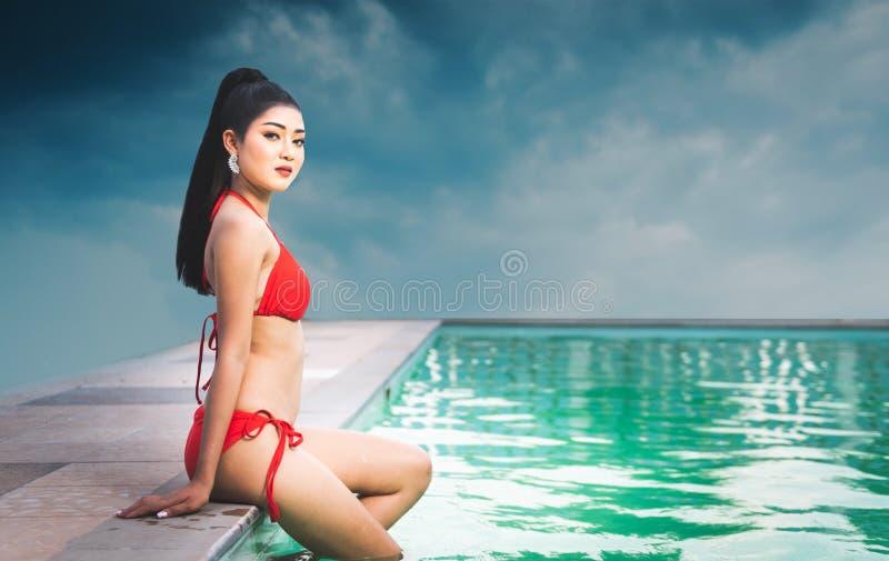 Piękny Azjatycki kobiety obsiadanie obok basenu plenerowego z czerwonym pływackim kostiumem zdjęcie stock