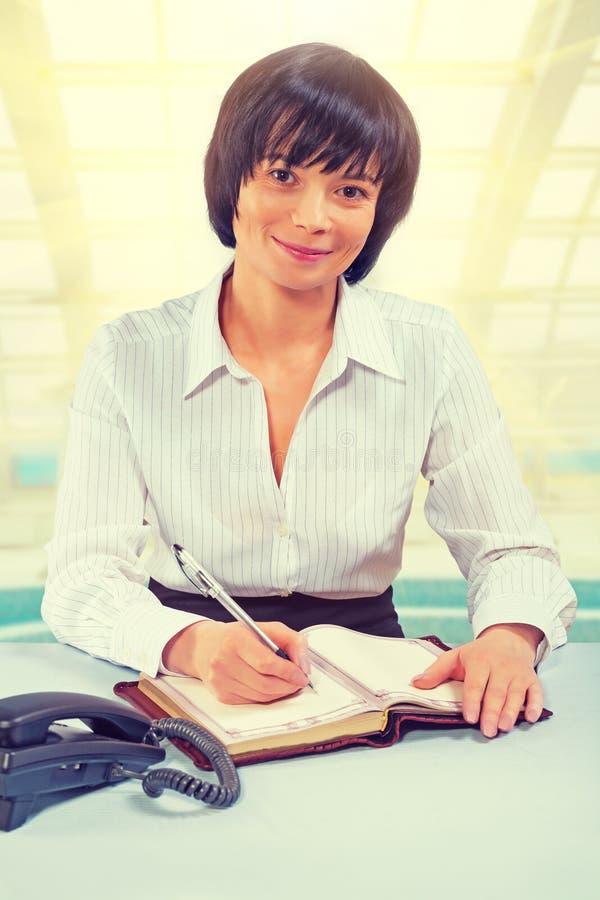 Piękny azjatykci bizneswomanu obsiadanie przy stołowym writing looki obraz stock