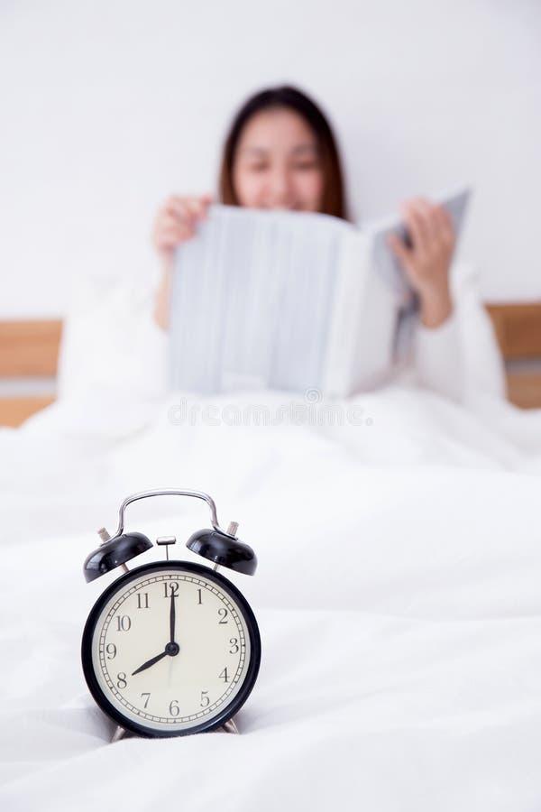 Piękny azjatykci kobiety kłaść i czytelnicza książka za budzikiem w łóżkowym sen zdjęcia royalty free