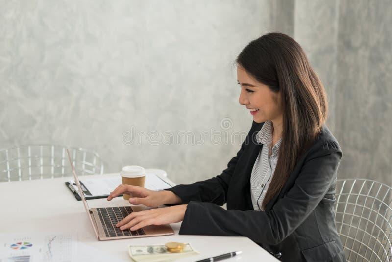 Piękny azjatykci młody bizneswoman pracuje na laptopie w jej wor fotografia stock