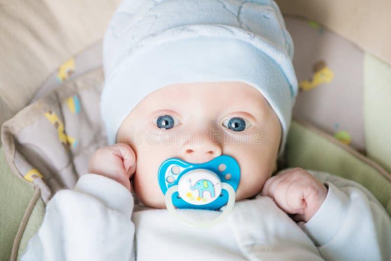 Piękny błękit dosyć przyglądał się dziecko dzieciaka z pacyfikatorem na złym i patrzeć kamerę w domu fotografia stock