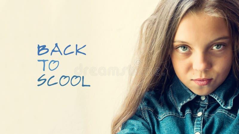 Piękny błękitnooki, blondynka nastolatka dziewczyna w cajgach koszulowych Na lekkim tle Inskrypcja z powrotem szkoła Zakończenie  zdjęcia royalty free