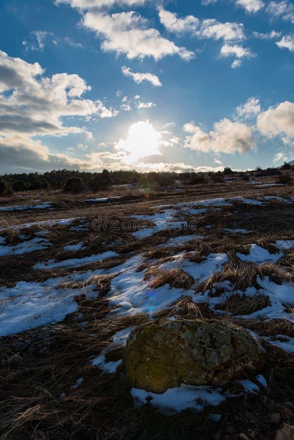 Piękny błękitny chmurnego nieba zimy krajobraz z kamieniem Zmierzch zdjęcia stock
