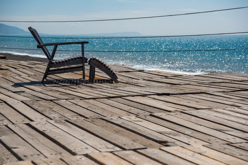 Piękny błękitny denny widok i drewniany relaksujący krzesło fotografia stock