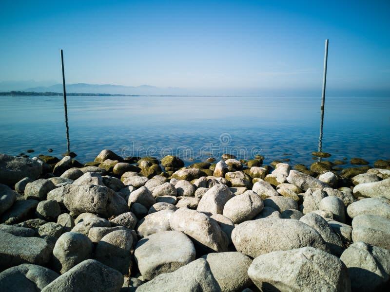 Piękny błękitny jeziorny tło z dużymi kamieniami obraz stock