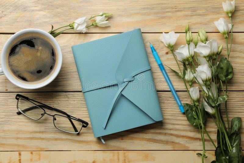 Piękny błękitny notatnik, filiżanka kawy, szkła i biali kwiaty na naturalnym drewnianym stole, Odg?rny widok obraz royalty free