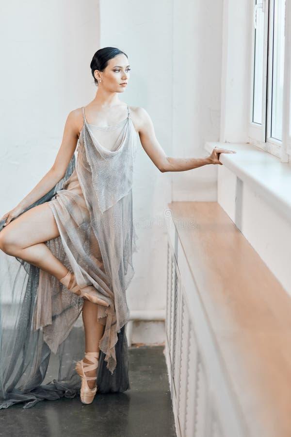 Piękny baletniczy tancerz z spławową tkaniny pozycją w pozycji blisko okno fotografia stock