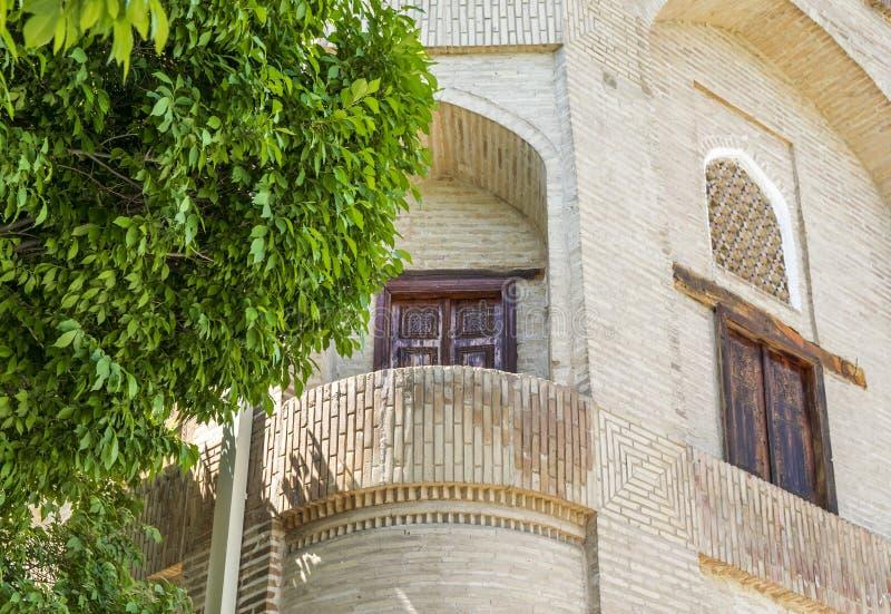Piękny balkon z antycznym drewnianym drzwi w PAMIĄTKOWYM kompleksie KHOJA BAHAUDDIN NAKSHBAND, Bukhara, Uzbekistan fotografia royalty free