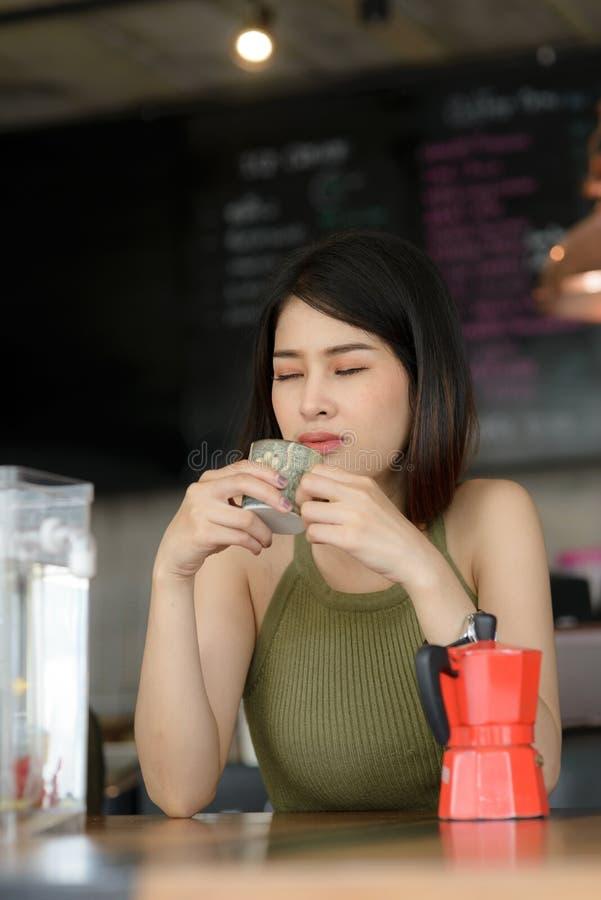 Piękny barista za kawa kontuarem i bada jej kawę, wor zdjęcia royalty free