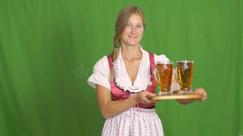 Piękny Bawarski kelnerki porcji piwo, patrzeje daleko od joyfully odizolowywający zdjęcia stock