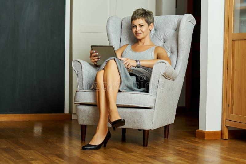 Piękny biznesowej kobiety obsiadanie na szarym krześle i pracy na pastylce fotografia stock