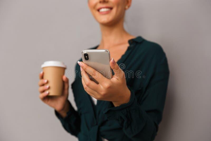 Piękny biznesowej kobiety pozować odizolowywam nad popielatym ściennym tłem pije kawę opowiada telefonem komórkowym fotografia royalty free