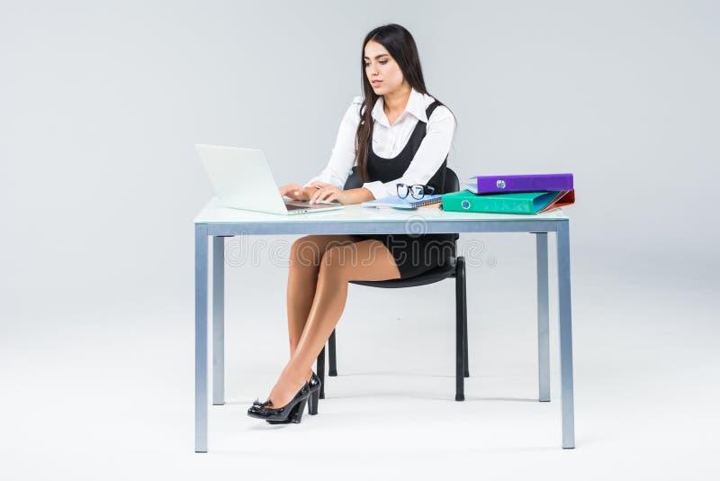 Piękny biznesowej kobiety uśmiechu obsiadanie przy biurkiem pracuje na laptopie odizolowywającym nad białym bac używać laptop pat fotografia royalty free