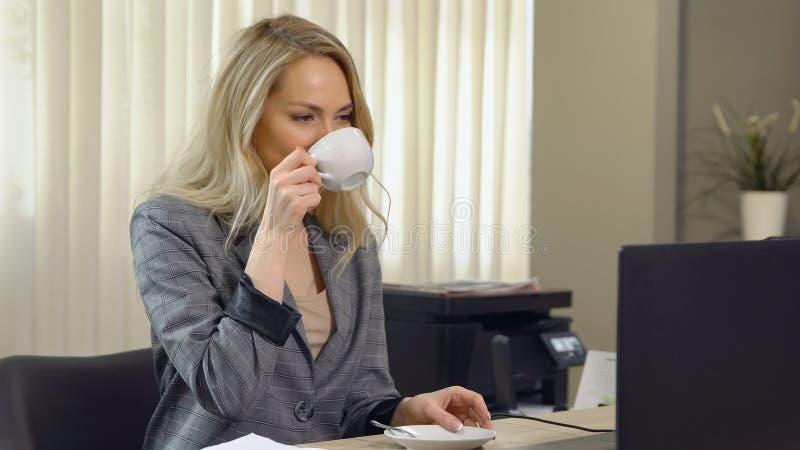 Piękny bizneswoman w kostiumu pracuje z filiżanki kawą przy miejscem pracy zdjęcie stock