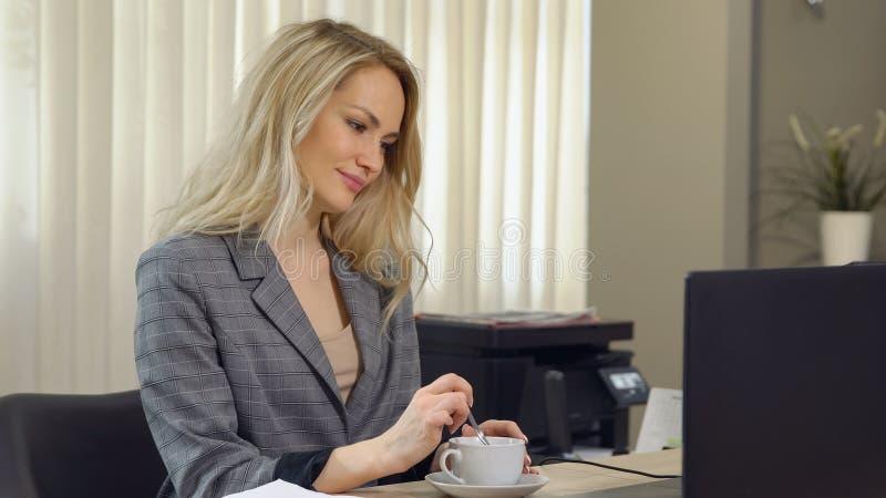 Piękny bizneswoman w kostiumu pracuje z filiżanki kawą przy miejscem pracy obrazy royalty free