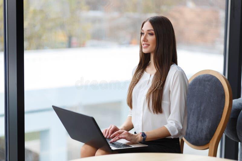 Piękny bizneswoman z laptopem w restauraci Damy obsiadanie blisko okno obraz royalty free
