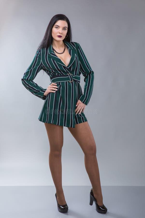 Piękny bizneswomanu studia strzał na popielatym tle Powabna i ufna poważna brunetki kobieta w zielonej kurtce obrazy stock