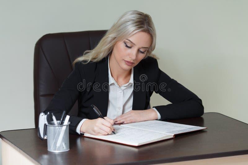 Piękny bizneswomanu writing w notatniku w biurze fotografia royalty free