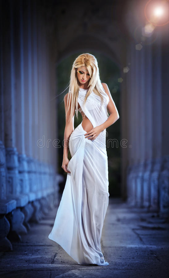Piękny blondynka anioł z świateł białych skrzydłami i biel przesłaniamy pozować plenerowy fotografia royalty free