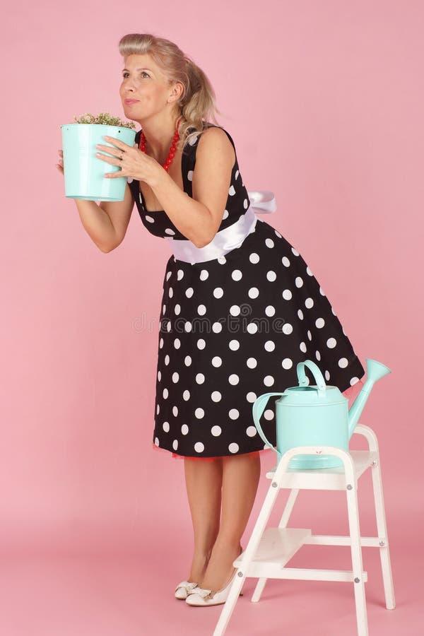 Piękny blondynki kobiety obwąchanie kwitnie, w górę stylu na różowym tle zdjęcie royalty free