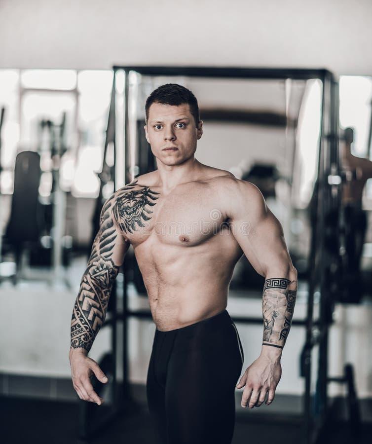 Piękny bodybuilder trener pokazuje daleko jego ciało zdjęcie stock