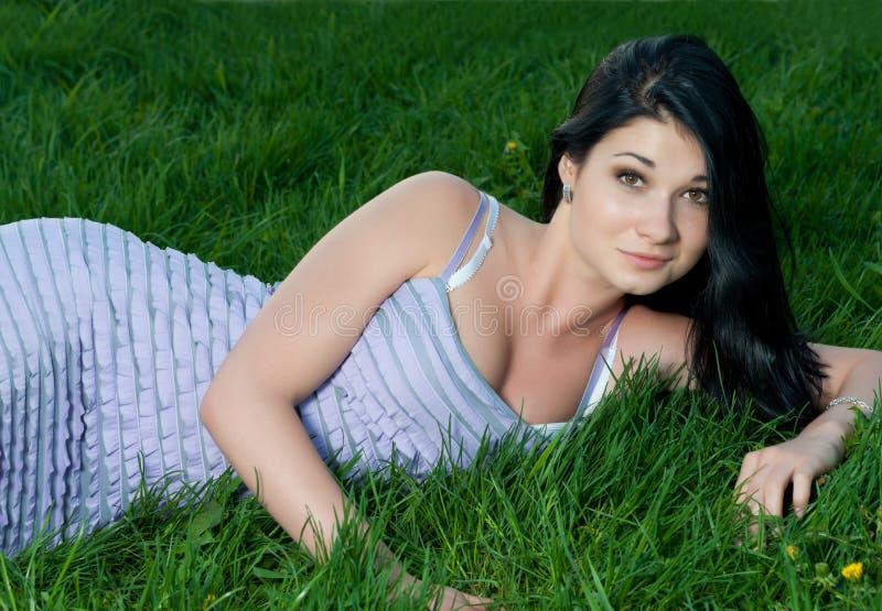 piękny brunetki dziewczyny trawy lying on the beach obraz stock