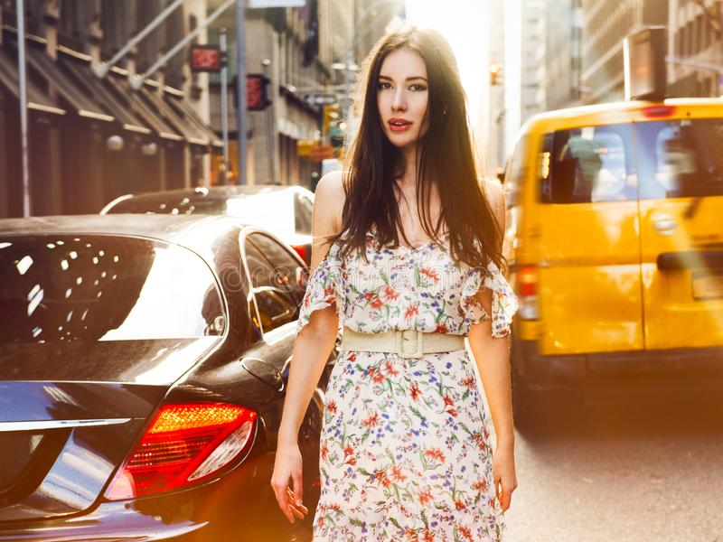 Piękny brunetki kobiety odprowadzenie na Nowy Jork miasta ulicie między samochodami jest ubranym lato suknię przy pogodnym letnim fotografia royalty free