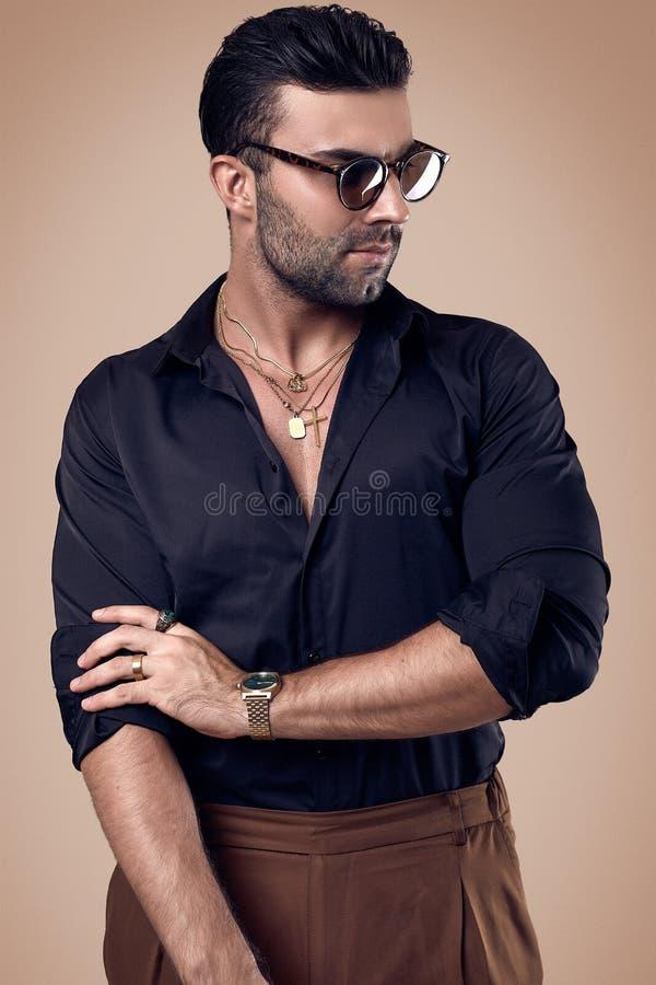 Piękny brutalny garbnikujący modnisia mężczyzna w czarnej koszula i szkłach zdjęcia royalty free