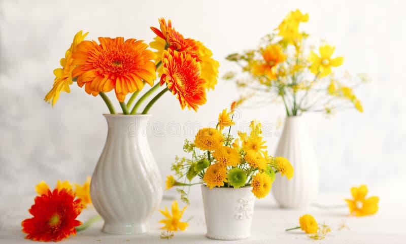 Piękny bukiet czerwień i kolor żółty kwitnie w białej wazie na drewnianym stole, frontowy widok Jesieni wci?? ?ycie z kwiatami zdjęcia royalty free