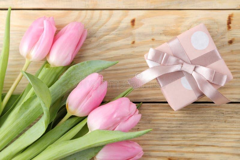 Piękny bukiet różowi tulipanów kwiaty i prezenta pudełko na naturalnym drewnianym tle Odgórny widok Wiosna wakacje fotografia royalty free