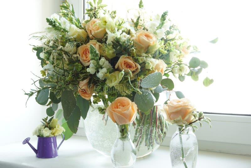 Piękny bukiet z delikatnie różowymi kwiatów stojakami na nadokiennym parapecie biały okno fotografia royalty free