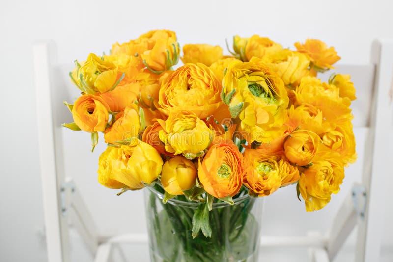 Piękny bukieta jaskier w szklanej wazie na białym tle kolorowy kolor mieszanki kwiat obrazy royalty free