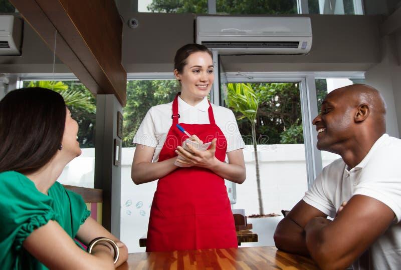 Piękny caucasian żeński kelner z gościami zdjęcia royalty free