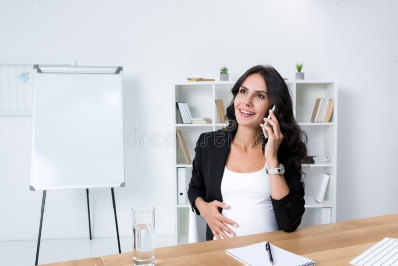 piękny ciężarny bizneswoman opowiada telefonem przy miejscem pracy obraz stock