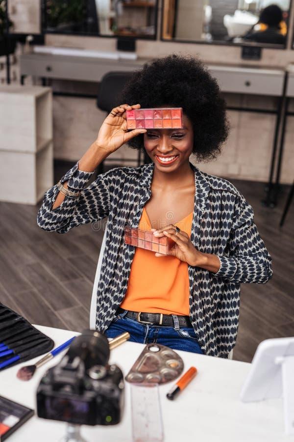 Piękny ciemnoskóry makeup blogger w pomarańczowy odgórny czuciowy komicznie zdjęcia stock