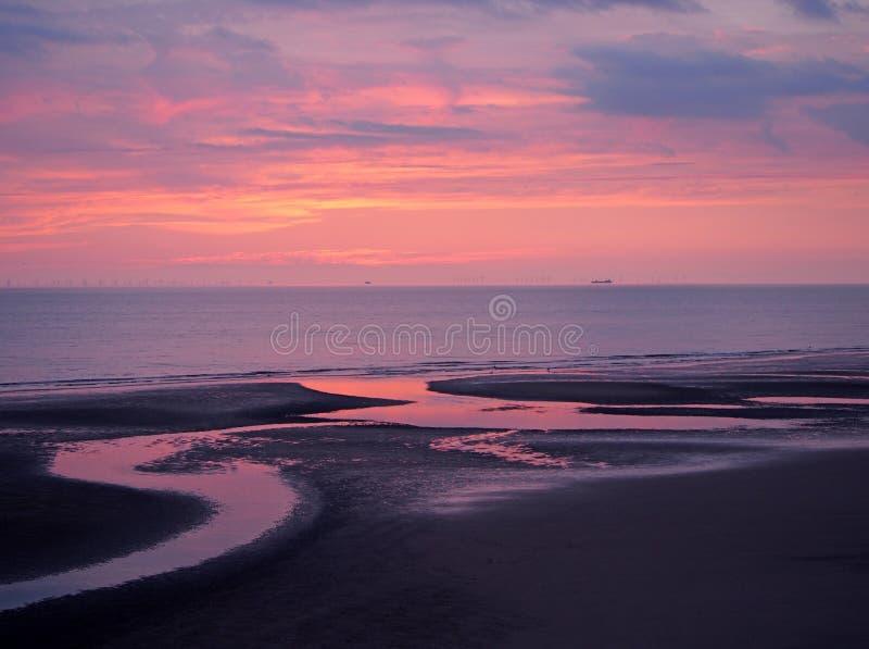 Piękny ciemny zmierzch nad spokojnym płaskim morzem z purpurowymi nieba i błękita chmurami odbijał w wodzie na plaży zdjęcie royalty free