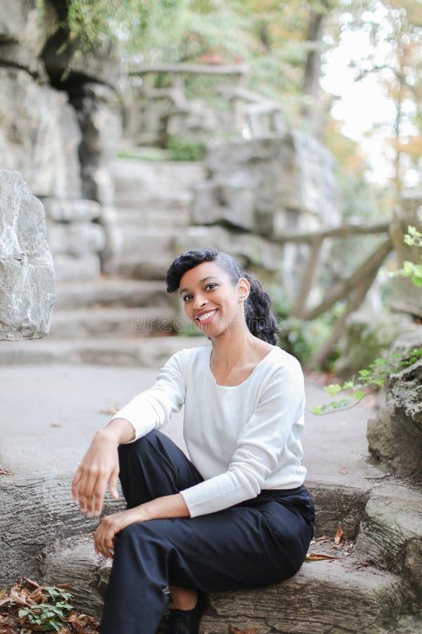 Piękny czarny żeńskiej osoby obsiadanie w parkowych pobliskich kamiennych schodkach i być ubranym białą bluzkę obrazy royalty free