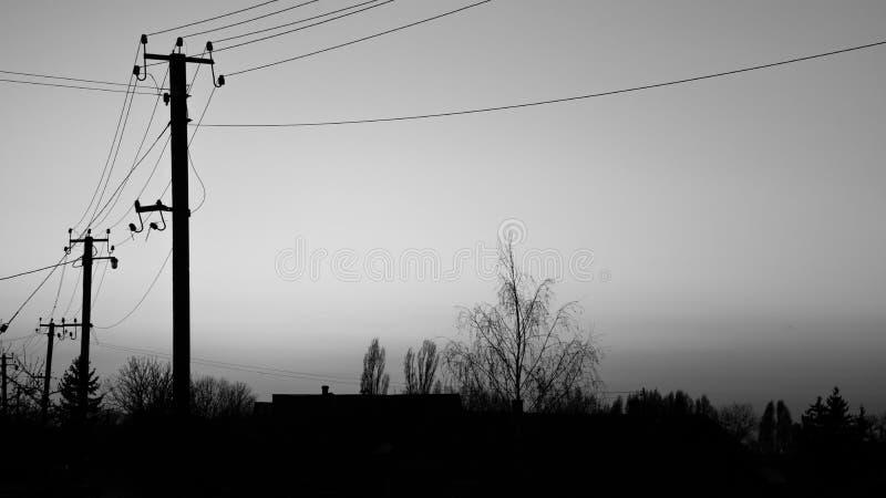 Piękny czarny lato zmierzchu zmierzch przeciw tło wiosce, budynkowi, drzewom i elektryczność liniom energetycznym, obraz royalty free
