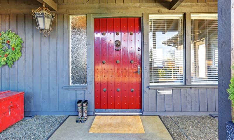 Piękny czerwony drzwi i boże narodzenie wystrój z popielatym drewnianym domem zdjęcia royalty free