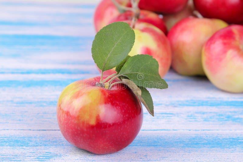 Piękny czerwony jabłko z zieleń liśćmi i udziałami jabłka w tle na błękitnym drewnianym stole obraz royalty free