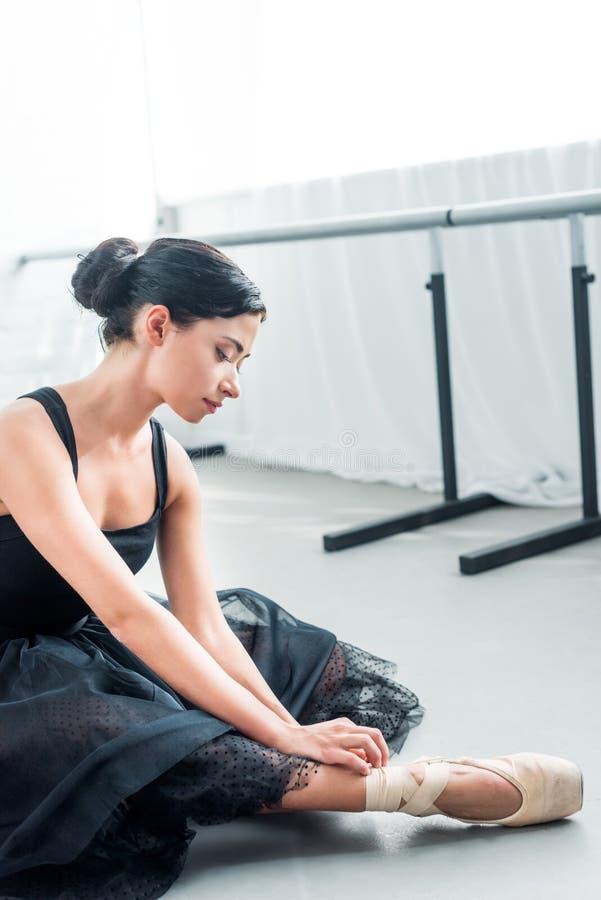 piękny czuły młody baleriny obsiadanie i wiązać pointe zdjęcie royalty free