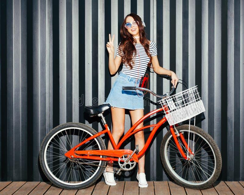 Piękny długonogi dziewczyna azjata w lato stroju, Amerykańskich okularach przeciwsłonecznych, kaseta graczu i hełmofonach pozuje  obraz stock
