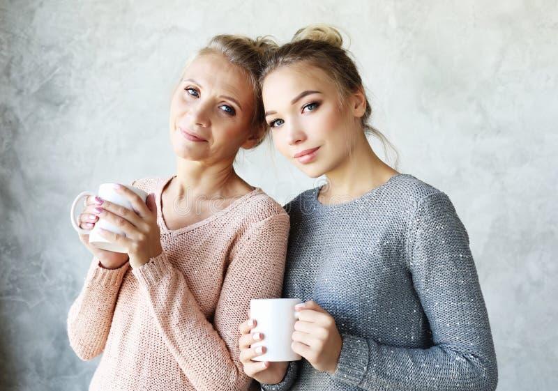 Piękny dorośleć macierzystego i jej dorosła córka pije kawę obraz royalty free