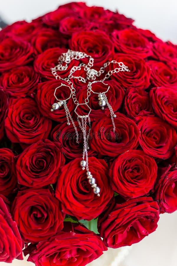 Piękny duży bukiet róże z jewellery worth w wazie na stole zdjęcie stock
